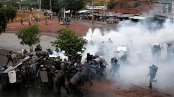 Police stand amid tear gas as they clash with supporters of opposition presidential candidate Salvador Nasralla in Tegucigalpa, Honduras, Monday, Dec. 18, 2017. President Juan Orlando Hernandez has been declared the winner of Honduras' disputed election, but that isn't quelling unrest from weeks of uncertainty as his main challenger calls for more protests Monday and vows to take his claims of fraud to the OAS. (AP Photo/Fernando Antonio)